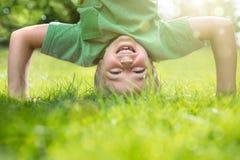 做在草的年轻男孩一headstand 库存图片