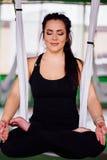 做在莲花坐的画象少妇反地心引力的瑜伽 空中航空飞行健身 白色吊床 免版税库存图片