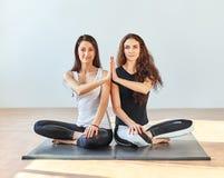 做在莲花姿势的两个少妇namaste在健身演播室 免版税库存图片