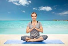 做在莲花姿势的妇女瑜伽凝思在席子 免版税图库摄影