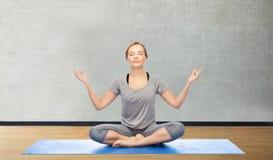 做在莲花姿势的妇女瑜伽凝思在席子 免版税库存照片