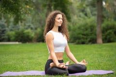 做在莲花的俏丽的妇女瑜伽凝思 免版税库存图片