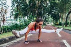 做在萤火虫postu的运动的适合的年轻女人手倒立锻炼 免版税库存图片
