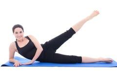 做在蓝色健身ma的年轻可爱的妇女健身锻炼 库存照片