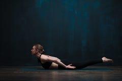 做在蓝色席子的年轻灵活的妇女瑜伽 图库摄影