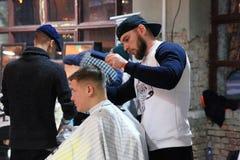 做在行家样式理发店的年轻人理发在K 免版税图库摄影