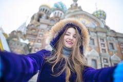 做在街道上的美丽的女孩selfie 库存照片