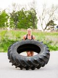 做在街道上的运动员轮胎轻碰锻炼 免版税库存图片