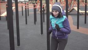 做在街道操场的耳机的女子运动员锻炼,缓慢的mo 股票录像