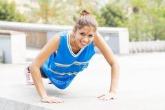 做在街道的微笑的美丽的运动妇女俯卧撑 图库摄影