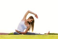做在街道的美丽的少妇瑜伽 库存图片