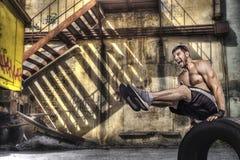 做在街道背景的年轻人平衡锻炼 免版税库存图片