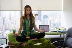 做在表上的女商人瑜伽凝思在办公室2 免版税库存图片