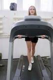 做在踏车的女孩锻炼 库存图片