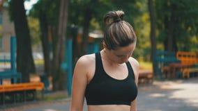 做在运动场的体育成套装备的年轻运动妇女脖子在公园 影视素材