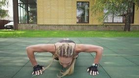 做在运动场的成人健身妇女俯卧撑 股票视频