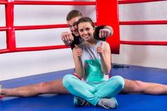 做在运动服的愉快的男性拳击手分裂在他的女朋友附近 库存图片