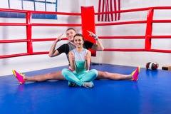 做在运动服的男性拳击手分裂在他的女朋友附近 库存照片