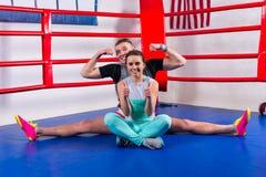 做在运动服的年轻男性拳击手分裂在他的女朋友附近 库存图片