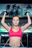 做在酒吧的女子运动员引体向上在健身房 免版税库存图片