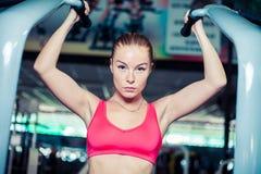做在酒吧的女子运动员引体向上在健身房 图库摄影