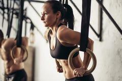 做在酒吧的女性成人引体向上在十字架适合的训练健身房 库存照片
