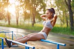做在酒吧晴朗室外的美丽的健身妇女锻炼 免版税图库摄影