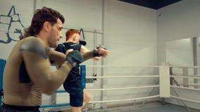 做在镜子前面的两架年轻战斗机专业培训动态锻炼在马戏团,侧视图 股票视频