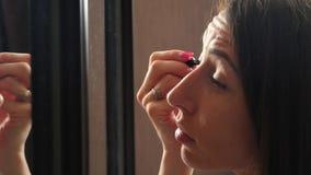 做在镜子前面的年轻美丽的妇女构成 影视素材