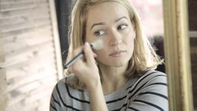 做在镜子前面的白肤金发的妇女每天构成,在她的与刷子的面颊上把粉末放 股票视频