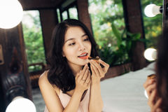 做在镜子前面的年轻美丽的亚裔妇女构成 图库摄影