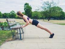 做在长凳的适合的妇女板条 免版税库存图片