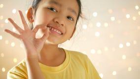 做在闪烁的轻的背景的亚裔小女孩好手势 股票录像