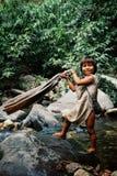 做在附近的小河的Kogi部族孩子洗衣店接近他们的家 免版税库存图片