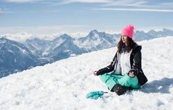 做在雪山的美丽的少妇瑜伽 免版税库存照片