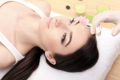 做在面孔的美容师的手射入 少妇得到秀丽在沙龙的面部射入 面孔老化,回复和 库存图片