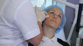 做在面孔的美容师的手射入 免版税库存图片