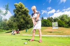 做在高尔夫球场的资深妇女发球区域冲程 免版税库存图片