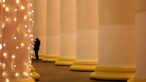 做在高溢出的专栏,圣诞节精神之间的游人照片 股票录像