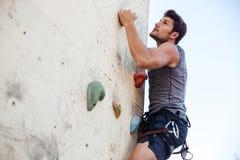 做在登山的年轻人锻炼在实践墙壁上 库存图片