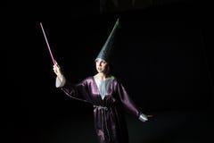 做在黑暗的背景的妇女魔术 库存图片