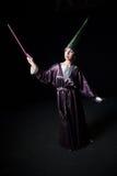做在黑暗的背景的妇女魔术 库存照片