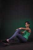 做在黑暗的背景的美丽的运动的妇女锻炼与绿色背后照明 库存照片