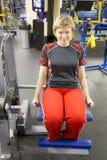 做在锻炼机器的成熟妇女供以座位的腿卷毛在健身房的健身锻炼期间 免版税库存照片