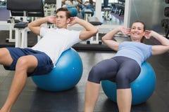 做在锻炼球的夫妇仰卧起坐 免版税图库摄影