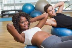 做在锻炼球的夫妇仰卧起坐 免版税库存图片