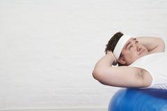 做在锻炼球的超重人仰卧起坐 免版税库存照片