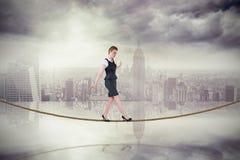 做在绳索的女实业家的综合图象一次平衡操作 库存照片