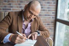 做在他的笔记本、经营计划或者日志文字的严肃的印地安人有些笔记 库存图片