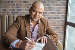 做在他的笔记本、经营计划或者日志文字的愉快的英俊的印地安商人有些笔记 免版税库存图片